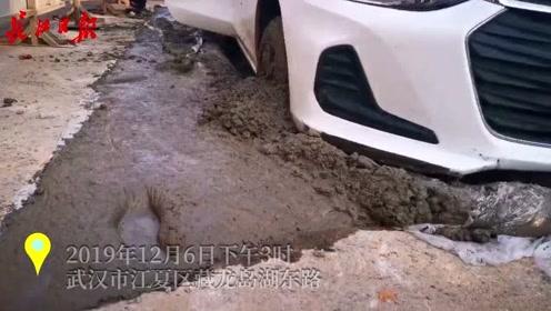 小车陷入维修道路厚厚水泥层,工地工人用挖掘机拖出