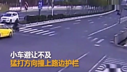 电瓶车闯红灯被小车撞飞一圈 小车猛打方向撞破路边护栏