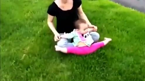 妈妈把萌娃放在草坪上,宝宝的脚死活不愿意着地,画面好逗