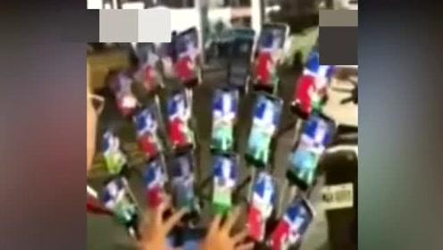 老大爷带着近二十部手机当街打游戏,路人们纷纷围观