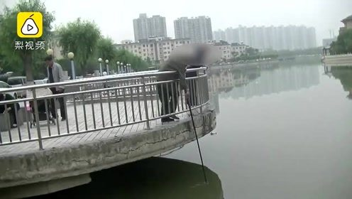 大妈湖边放生男子一旁捞鱼 两方起冲突争吵