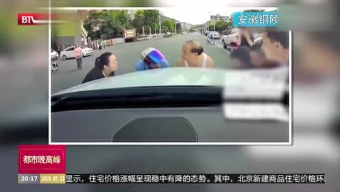 路人被卷车底 众人赶来奋力抬车救人