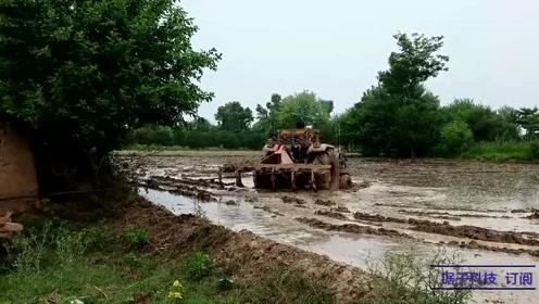 拖拉机强行耕犁,结果陷进泥坑出不来,司机急坏了,看看怎么救援