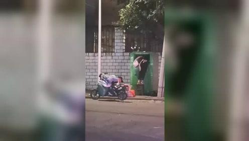 南宁街头旧衣物捐赠箱被人乱翻 两人装满一大袋后离开