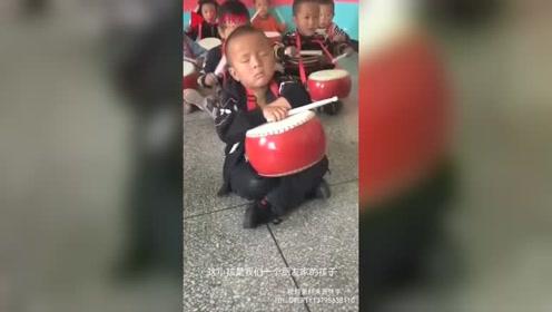 睡神附体!小男孩表演中坐地上打瞌睡 同学打鼓都没吵醒