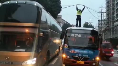 早高峰,交警站公交车顶双手托举电缆疏导交通