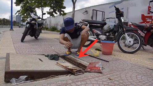 小伙打开路边下水道井盖,鱼钩放下去钓鱼,你猜能钓到吗?