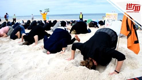 澳洲海滩近百人将头埋入沙中场景奇特 背后原因令人深思