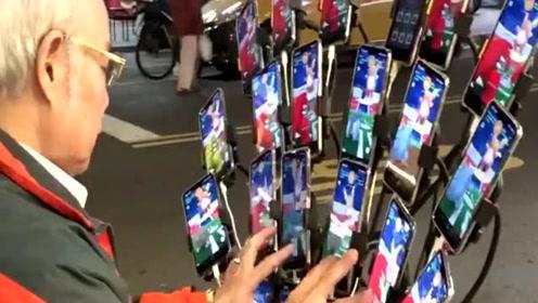 游戏达人狂秀操作 老伯街头操控22部手机狂抓宝可梦