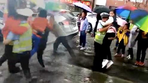 暴雨后街道变河,执勤交警挨个抱孩子上学