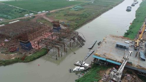 航拍在建桥梁垮塌现场,硕大箱梁整体塌入水中,十多名工人落水