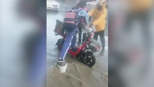 """大雨致积水太深 外卖小哥用电动车当""""垫脚石""""扶行人过马路"""