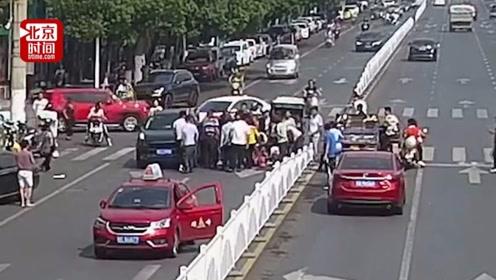 女子骑车逆行被车撞翻又遭另一车卷入车底 众人合力抬车上演52秒生死营救