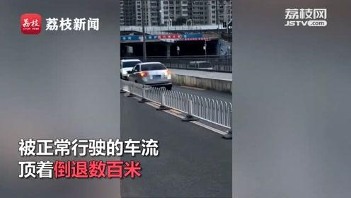 逆行轿车被车流顶着倒退数百米,网友:看你下回还敢不敢逆行