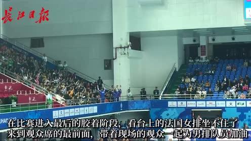 法国男排在赛场上拼杀,女排队员在场外带着观众助威加油