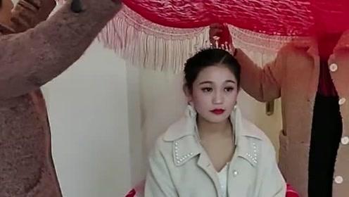 不知这是哪里的风俗,在新娘子的头上盖上红布,这样显得更加上档次!