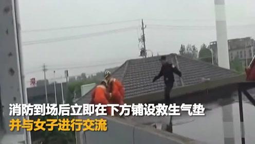女子携剪刀坐楼顶欲轻生 消防员趁其不备将其救下