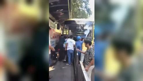 公交车撞站台将老人和小女孩卷入车底 众人合力抬车救人