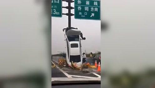 高架上小车垂直开上标志杆 女司机一脸无奈蹲路边
