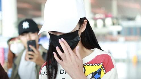 傅菁穿卡通条纹毛衣现身机场口罩遮面独露迷人双眼