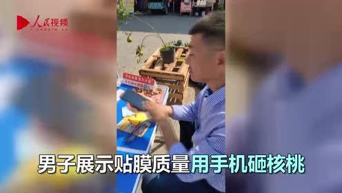 """牛!男子为展示贴膜质量 现场表演""""手机拍核桃"""""""