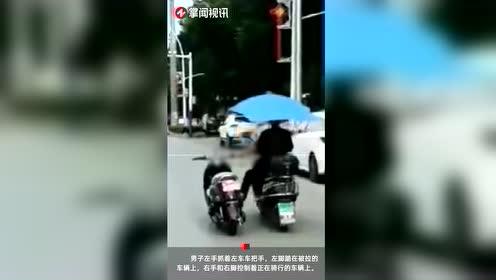 男子骑摩托左右开弓 左手扶车右手举雨伞