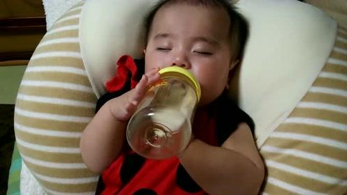 5个月的宝宝喝着奶睡着了,奶瓶掉了就又塞回去,真是小吃货一枚啊!