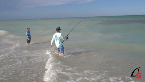 两男子在海边,一人拿着鱼竿钓鱼,一人在旁边看着!