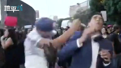 墨西哥记者游行现场遭民众怒吼后 又突然被陌生男子一拳打倒在地