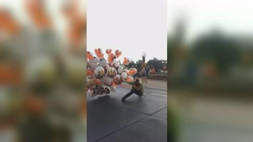 迪士尼乐园狂风大作,气球售卖员险些被吹跑