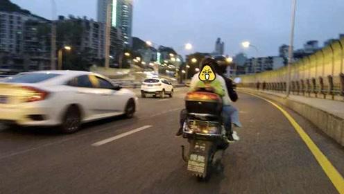 危险动作!小孩倒坐摩托车,一路捧着手机玩不听劝