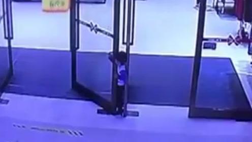 男童钻玻璃门遭卡脖子进退两难 监控拍下揪心瞬间