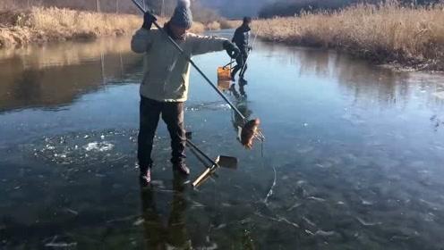 冬季的正确捕鱼方式,直接在河面上砸个窟窿出来