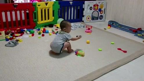 想要得到远处的玩具,11个月的宝宝突然站起来,惊讶后自己鼓掌