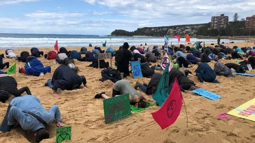 环保人士花式抗议出新招 头埋沙堆抗议气候恶化