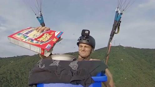 太惬意了!男子乘滑翔伞坐在半空中享受起了美食