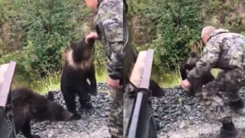 男子醉酒后伸手逗弄野生小熊 手被咬住差点被拖走