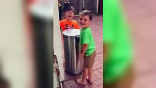 2名男孩轮流用垃圾桶盖互打脸 玩得不亦乐乎