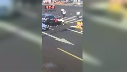 老太骑车被卷进车底 警民飞奔而来合力抬车救人