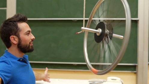 老外用一根绳子吊着车轮,车轮就能转动起来,背后有啥原理呢?