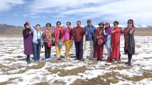 青海祁连山风景醉人:雪山脚下花盛开,游客雪地欢呼拍照