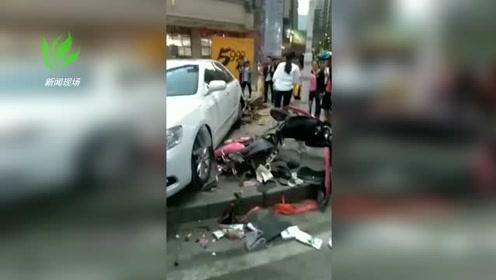 一辆白色小车倒车时突然穿上人行道 一辆电动车被撞烂