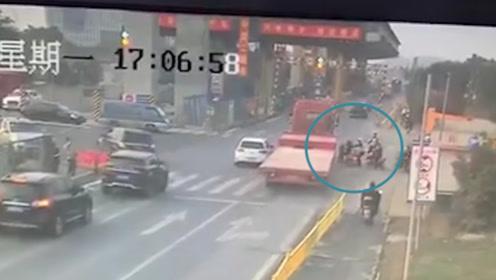 好险!电动车突然起步遇上大货车抢黄灯 生死关头被辅警一把拉回