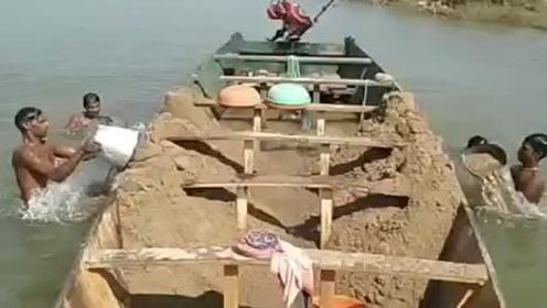 拉沙的船来了,小伙子们一桶一桶往上挖,有点费劲啊!