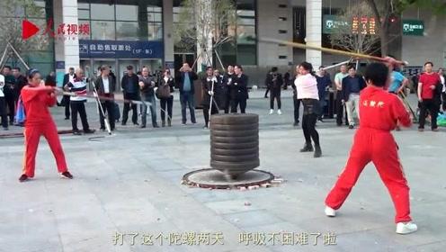 广场健身又出新花样 老人组队抽打1960斤巨型陀螺引围观