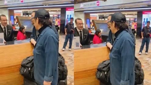 56岁李连杰和助理现身机场,一头黑发状态好,刻意回避镜头