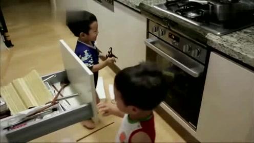 书俊拿着黑色小铁人敲打烤箱,书言拿着餐具逗书俊