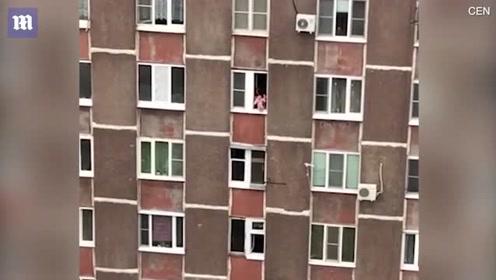 母亲将婴儿悬在窗外 称为让其呼吸新鲜空气