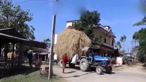满载干草的拖拉机,碰触到了电线短路起火,场面触目惊心!