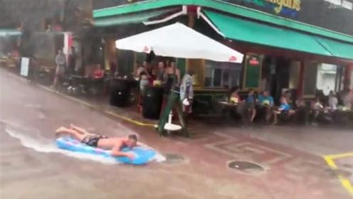 西班牙度假者遇暴雨苦中作乐 街道上趴气垫玩冲浪